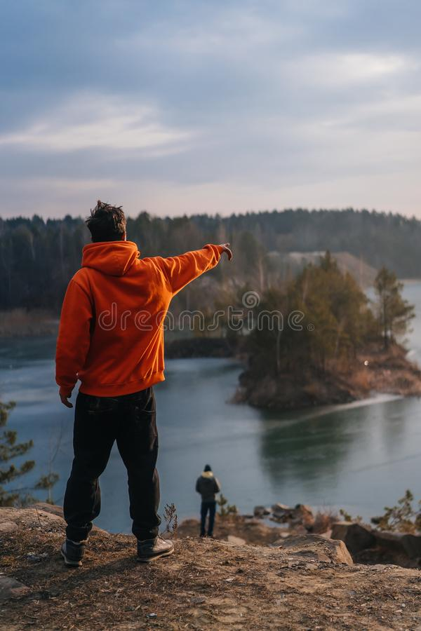 在峭壁边缘的一个年轻人身分为照相机摆在 免版税库存图片
