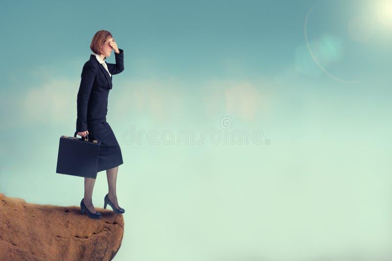 在峭壁边缘的女实业家 免版税库存图片