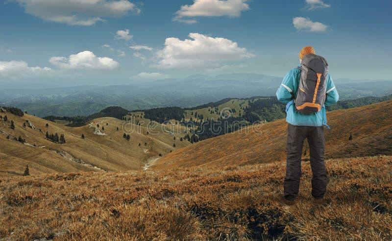 在峭壁顶部的远足者敬佩风景的 免版税库存图片