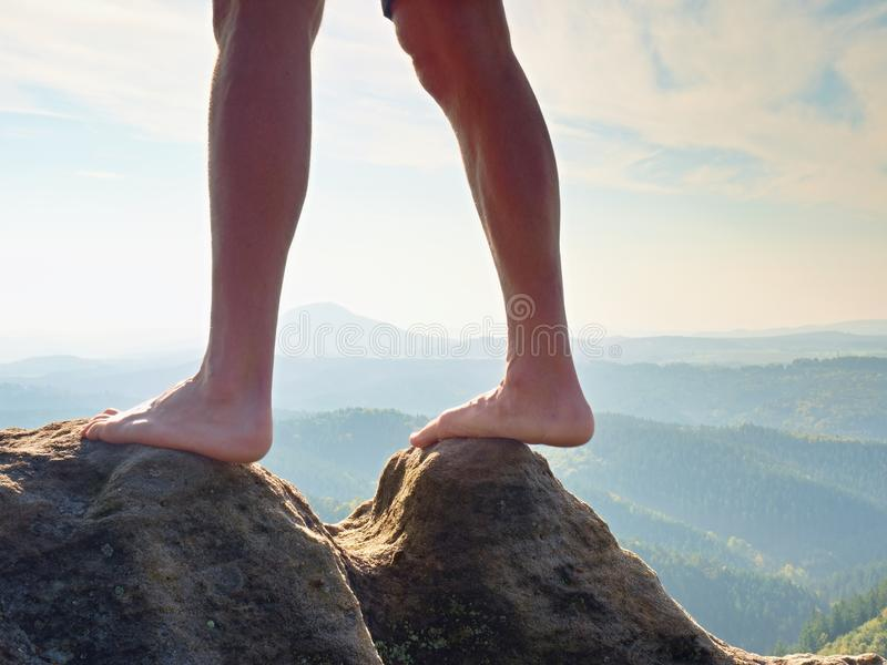 在峰顶的赤裸男性腿做步 在谷上的砂岩岩石与疲乏的远足者腿 库存照片