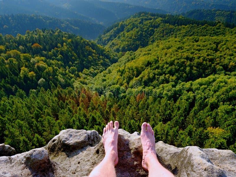 在峰顶的赤裸男性腿做步 在谷上的砂岩岩石与疲乏的远足者腿 免版税库存图片