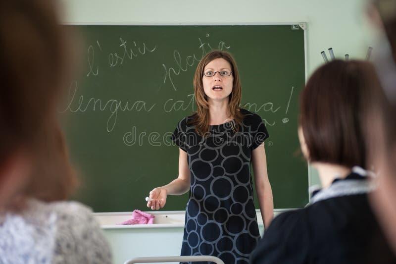 在州立大学的西班牙语教训 老师是一年轻有吸引力苗条的 免版税库存照片
