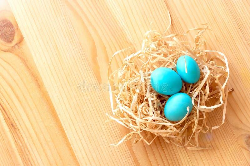 在巢的三个蓝色鸡蛋在轻的木背景 复活节庆祝概念 免版税库存图片