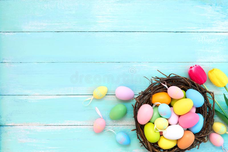 在巢的五颜六色的复活节彩蛋与郁金香在蓝色木背景开花 免版税库存照片