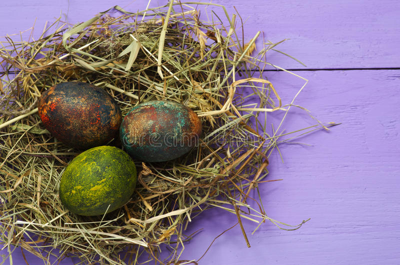 在巢的复活节彩蛋在木背景 免版税库存图片