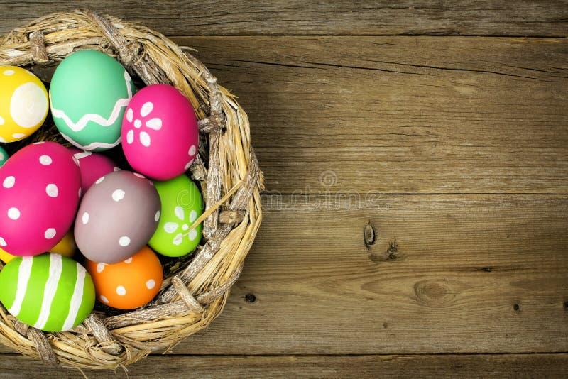 在巢的复活节彩蛋在木头 免版税库存图片