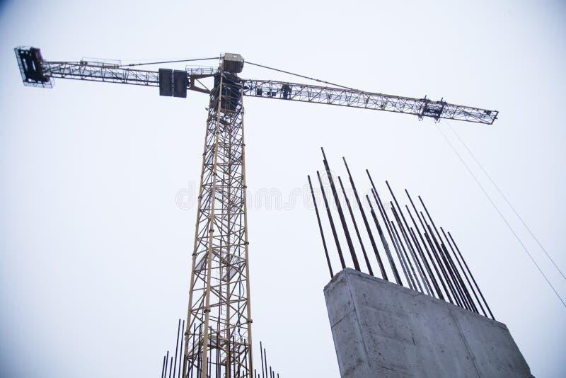 在工业建造场所的混凝土桩 摩天大楼大厦有起重机、工具和被加强的铁棍的 免版税库存照片