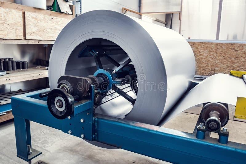 在工业形成的机器的金属板卷在工厂车间、不锈钢和金属制品制造业 图库摄影