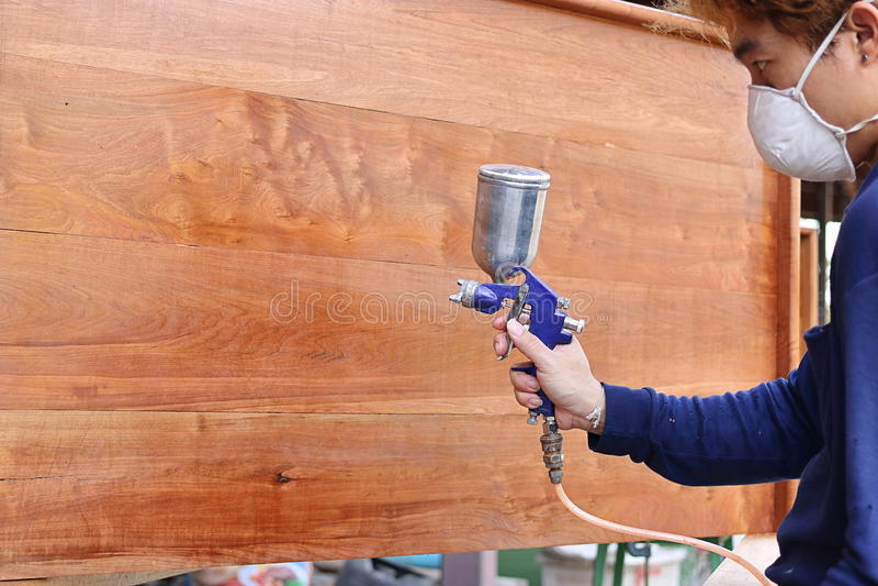 在工业画家的手上的选择聚焦有绘有喷枪的安全面具的一套木家具在家庭车间 掩饰的 免版税库存图片