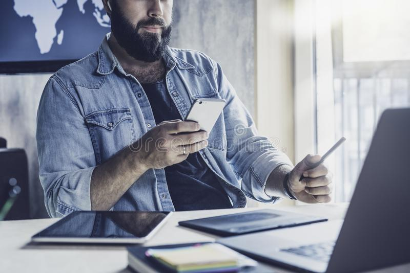 在工作中使用数字设备和小工具的项目经理 在手机上查看电子邮件和发送消息的人 库存图片