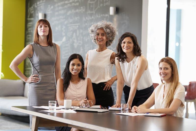 在工作会议上微笑对照相机的五个女性同事 库存照片