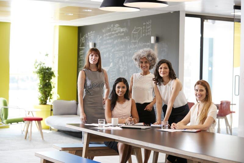 在工作会议上微笑对照相机的五个女性同事 库存图片