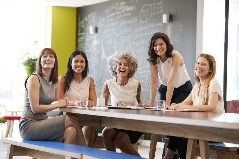 在工作会议上微笑对照相机的愉快的女性同事 库存照片