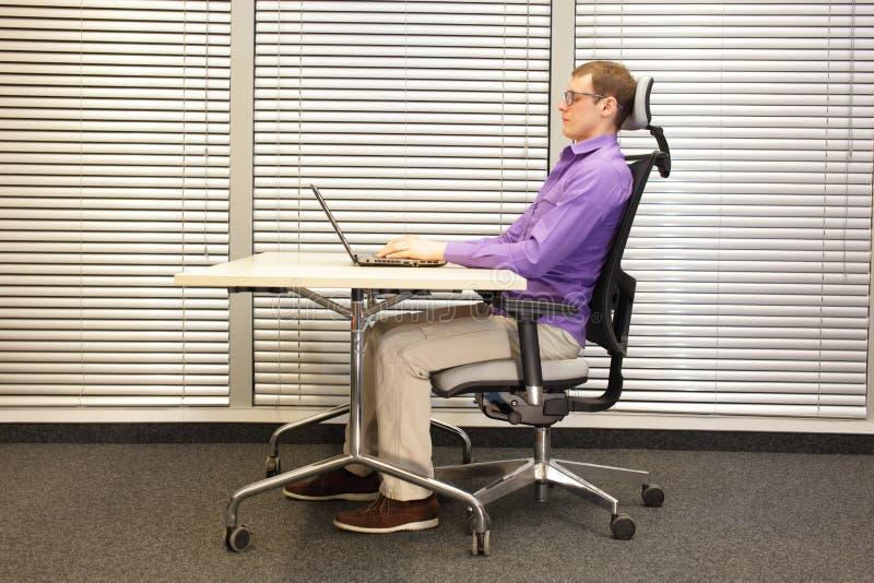 在工作区的正确的坐姿 椅子的人与膝上型计算机一起使用 免版税库存图片