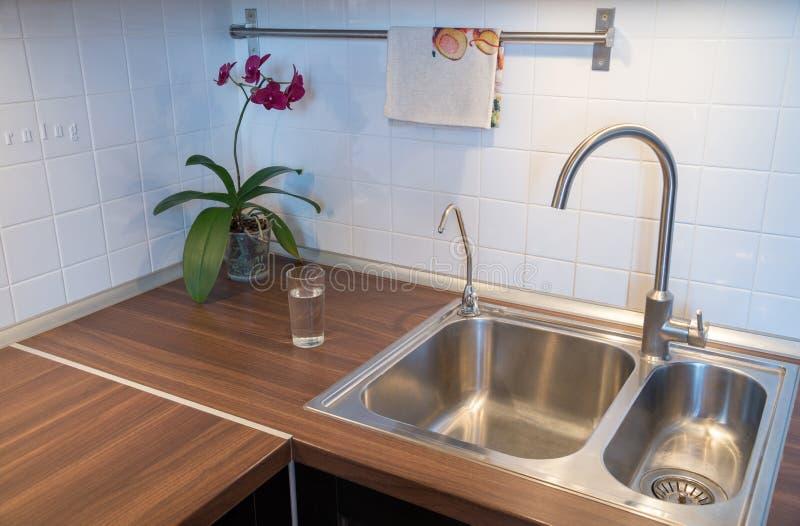 水在工作台面的在现代厨房里 库存图片