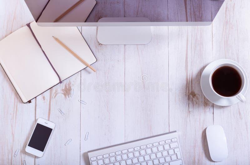 在工作场所概念、个人计算机计算机显示器智能手机、键盘、开放笔记本和咖啡的办公设备在白色木桌上 库存照片