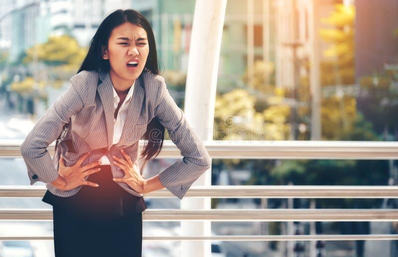 在工作期间,一个亚裔女商人有严厉胃肠痛苦 免版税库存照片