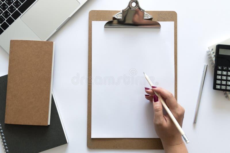 在工作的书桌妇女的顶视图移交它文字战略 工作场所的平的位置包含膝上型计算机,纸,笔记本,笔 库存图片