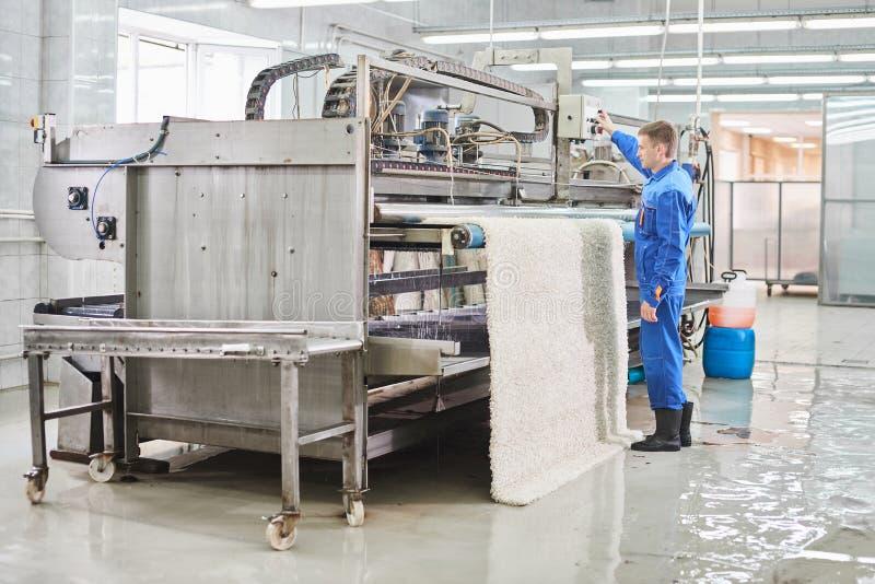 在工作的洗衣店工作者在地毯洗涤物的自动机器过程中 库存图片