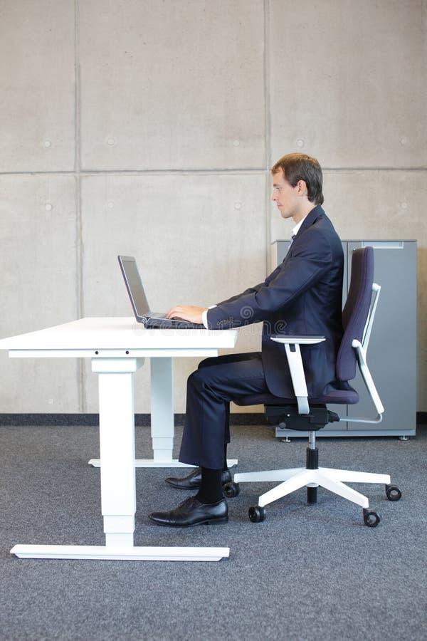 在工作站-衣服的人的正确坐姿- 免版税库存照片