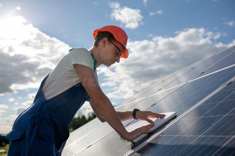 在工作者和太阳电池板的侧视图 免版税库存照片