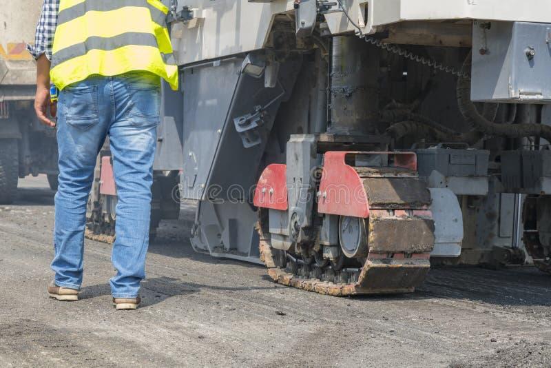 在工作者和涂柏油的机器的接近的看法 柏油路的机械 图库摄影