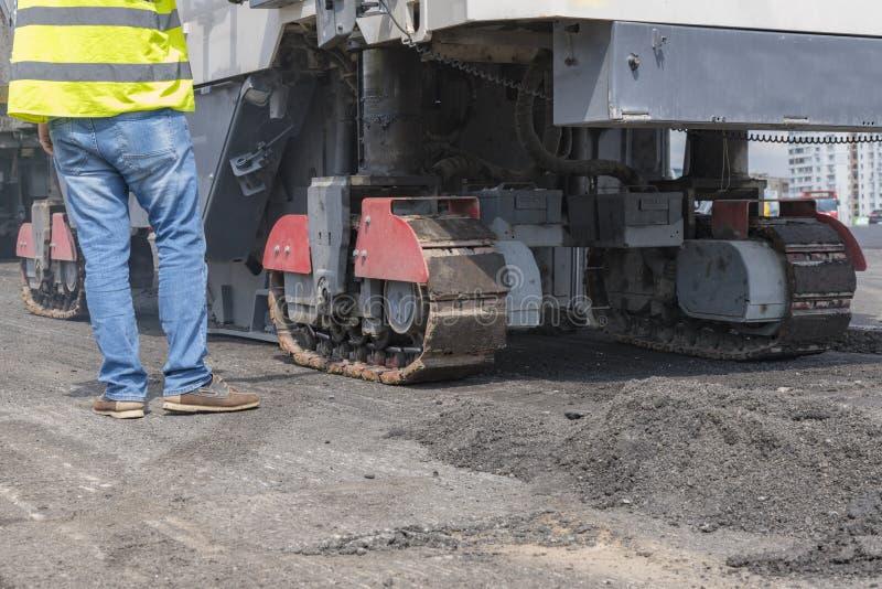 在工作者和涂柏油的机器的接近的看法 柏油路的机械 库存图片