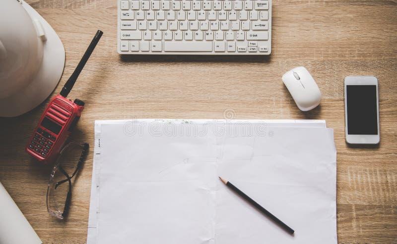在工作表上的工程学工具为工程项目 一件白色盔甲和图纸 库存照片