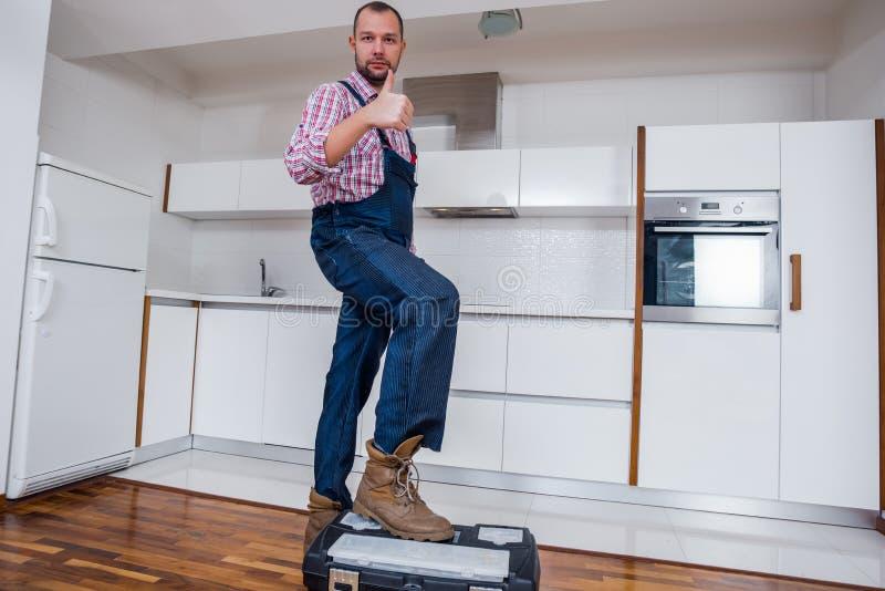 在工具箱上的工作员身分在厨房里 库存图片