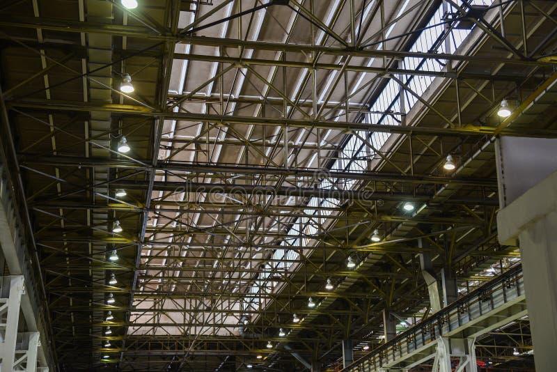 在工厂厂房的天花板平板,顶房顶钢结构与现代仓库或工厂灯  免版税库存照片