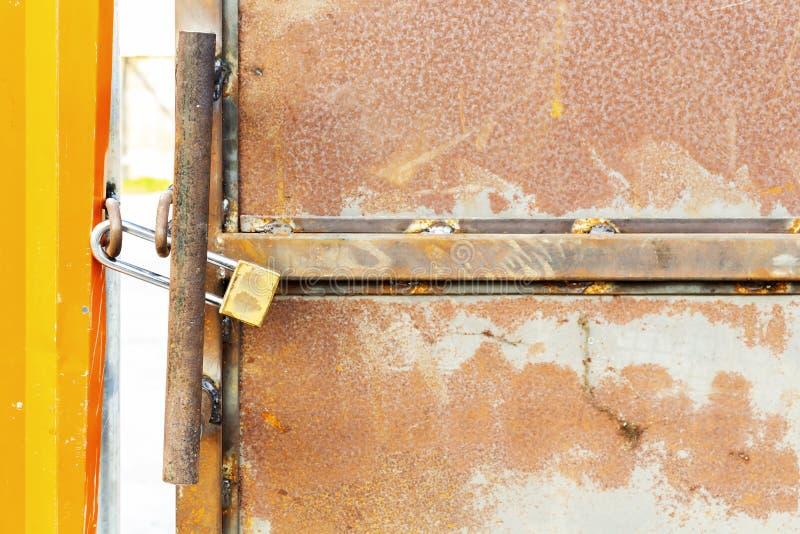 在工厂b生锈的金属钢门的老锁着的挂锁  免版税库存图片