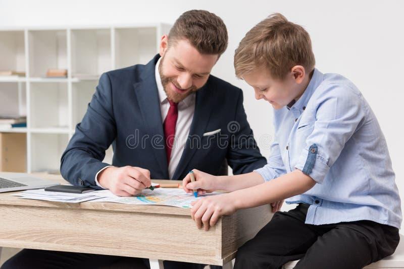 在工商业票据的商人图画与儿子 库存照片