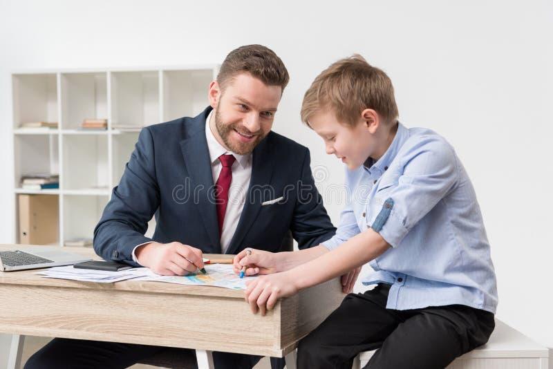 在工商业票据的商人图画与儿子 免版税库存图片