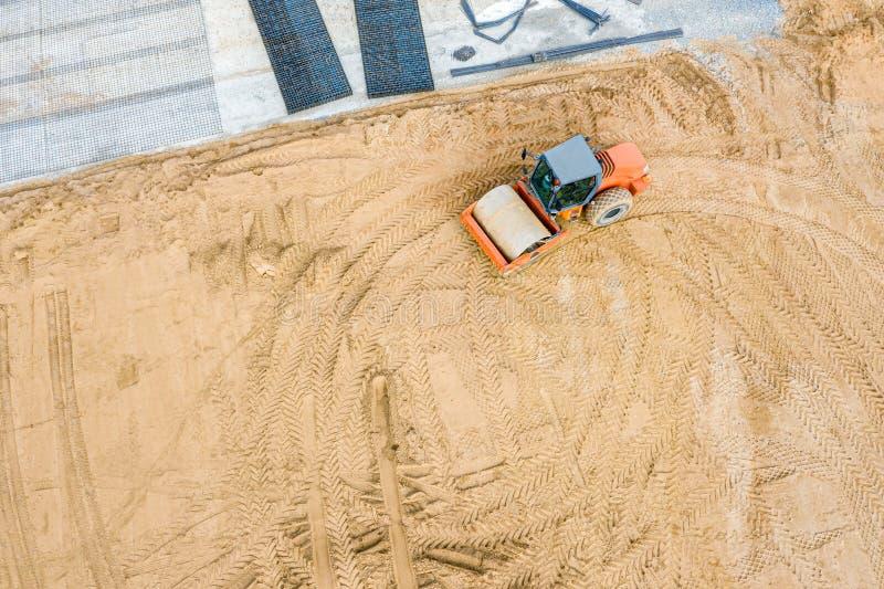 在工地工作的压路机 成水平在道路施工工作前的沙子 库存图片