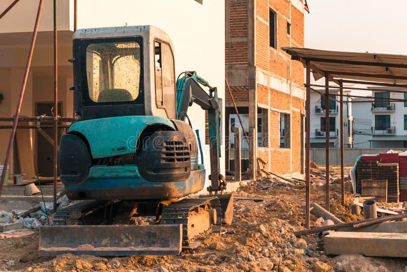 在工地工作的微型挖掘机 挖掘机在房子附近调控地形 库存照片