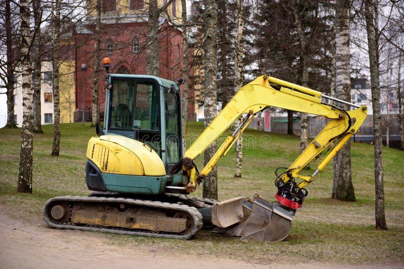 在工地工作的微型挖掘机 挖掘机在被开掘的孔附近站立 免版税库存照片