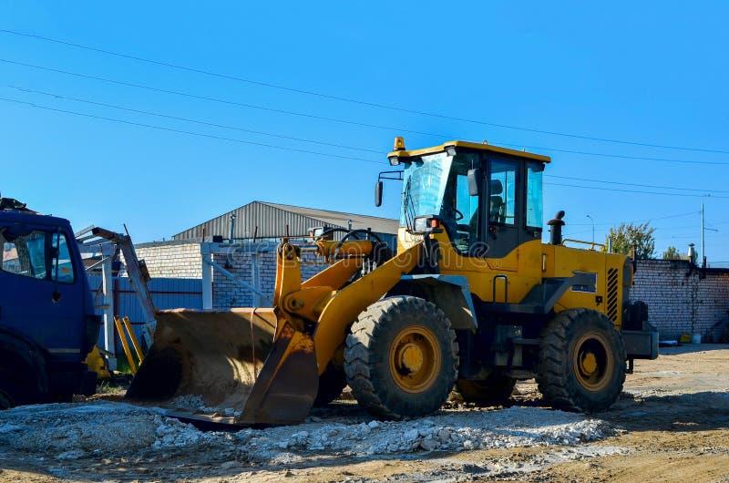 在工地工作的挖掘机准备装载土壤入翻斗车 与铁桶的轮子装载者 免版税库存图片