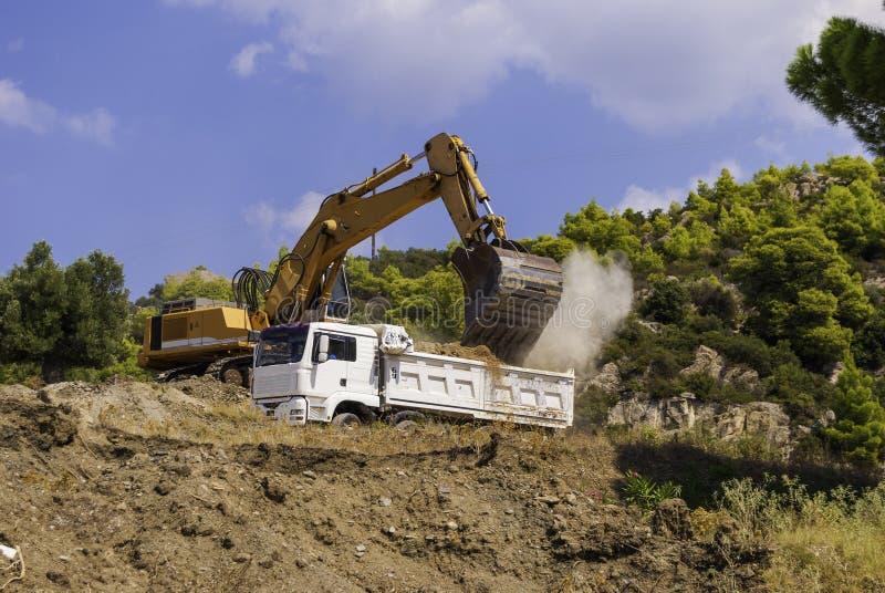 在工地工作装载的黄色挖掘机土壤到一辆白色翻斗车的身体里 免版税图库摄影