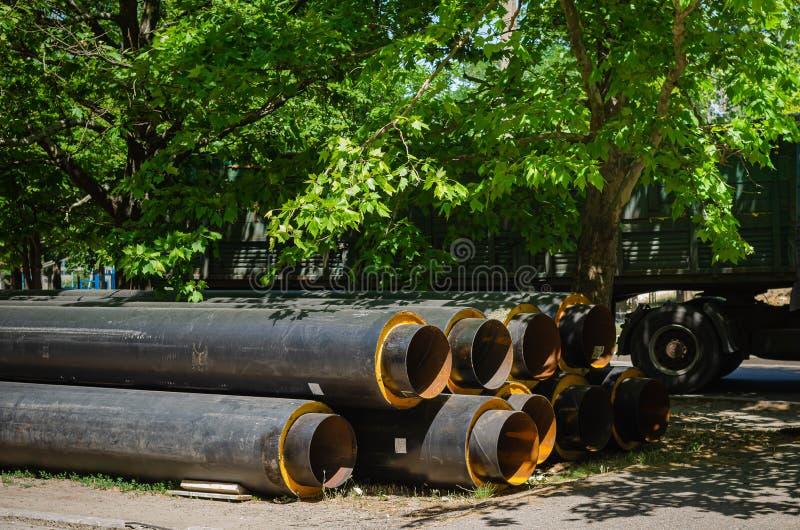 在工地工作附近的大直径供水的管子 取代通信 免版税图库摄影