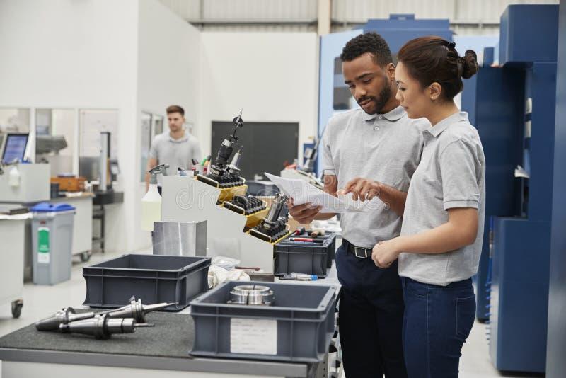 在工程学车间地板上的工程师和学徒集会  免版税库存图片