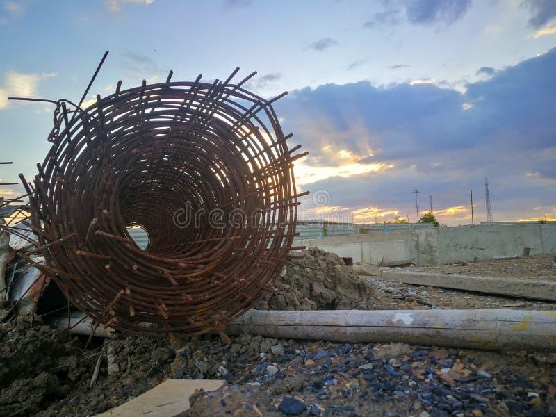 在工程项目的生锈的钢卷 钢和竹子在黏土和石堆 库存照片