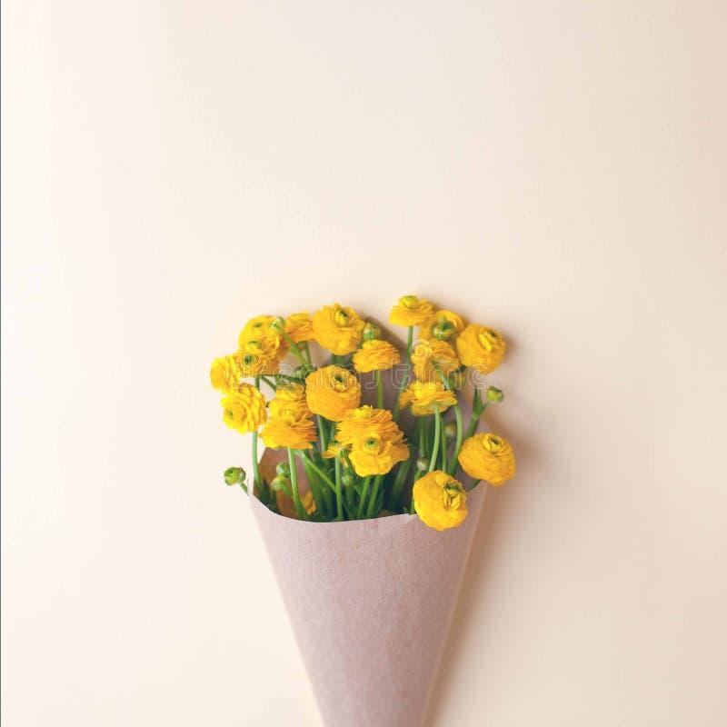 在工艺纸包裹,最小的春天夏天背景,母亲,妇女天,浪漫概念的黄色花 免版税库存图片
