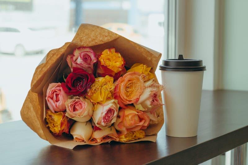 在工艺纸和咖啡包装的新鲜的五颜六色的玫瑰美丽的花束去托起在一张桌上在咖啡馆 库存照片