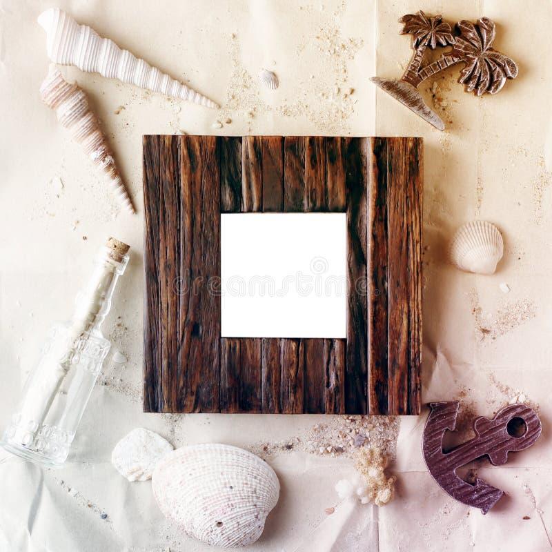 在工艺纸的葡萄酒木照片框架与沙子和海壳嘲笑  免版税库存照片