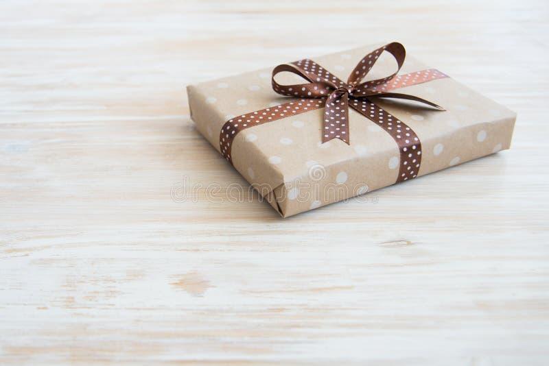 在工艺纸,在木桌上的eco纸的箱子 顶视图 有缎丝带弓的布朗包装纸礼物盒在老土气wo 免版税库存照片