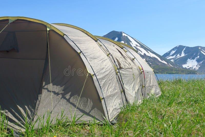 在左下角身分的大帐篷在绿色领域背景中高山的许多美丽的曲线和 库存图片