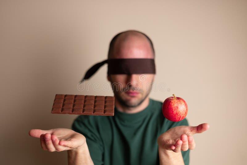 在巧克力块和苹果下的蒙住眼睛的人位置手 免版税图库摄影
