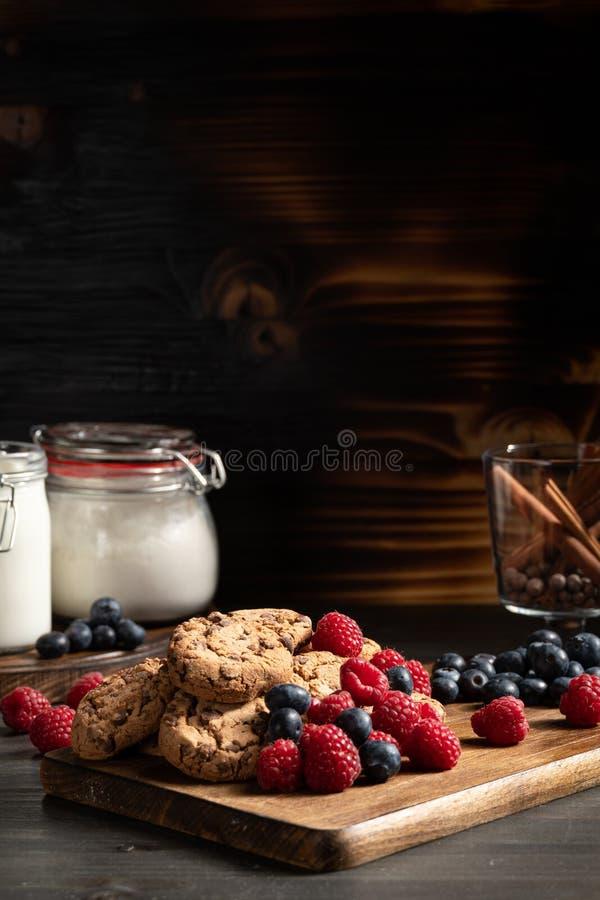 在巧克力饼干旁边的新鲜的莓果在木背景 库存照片