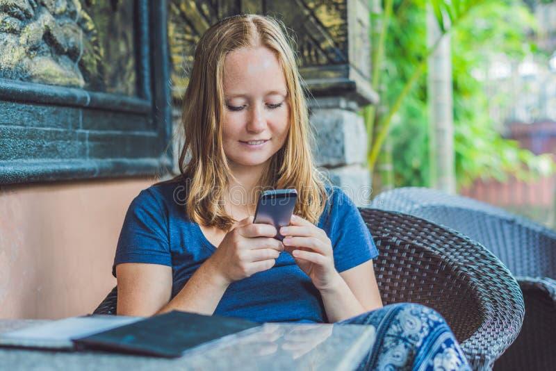 在巧妙的电话的妇女键入的正文消息在咖啡馆 15个妇女年轻人 库存照片