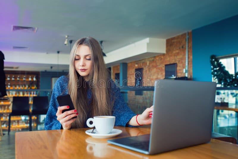 在巧妙的电话的妇女键入的正文消息在咖啡馆 坐在一张桌上的少妇用咖啡使用手机 免版税库存照片